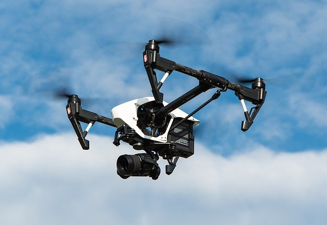 drone with camera flying with blue cloudy sky in background