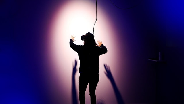 Photograph of a person wearing a virtual reality VR headset standing in front of a wall casting a silhouette