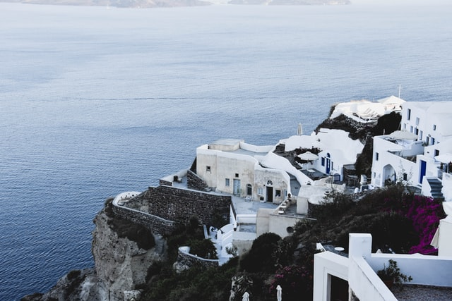 Photograph of the end of Santorini island, Oia Greece, with the sea in background and white house in foreground