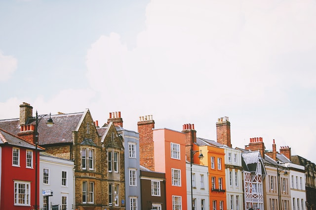 Photograph of a row of city terraced houses of various architectural styles in Oxford, England UK with a view upwards towards a bright sky