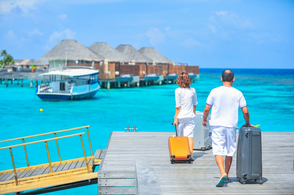 man and woman walk on dock to holiday hotel