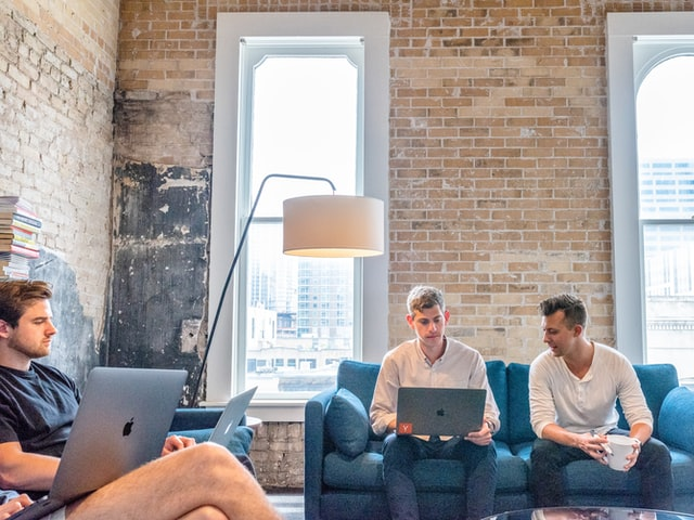 Three men using Macbooks sitting on sofas in a photo: Marketing team meeting at a startup co-working space strategizing the next social media campaign at Proof Technologies Inc, East 6th Street, Austin, Texas, USA | Image credit: Austin Distel — Unsplash