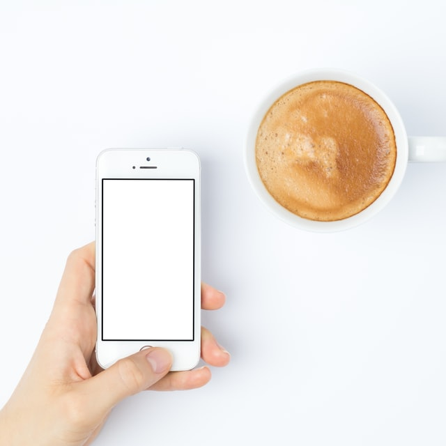 Person holding a white iPhone 5S/SE with blank screen next to a frothy coffee on white table birds eye photograph