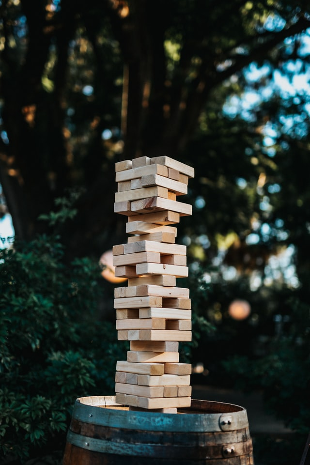 Jenga topple block stack outside placed on a wooden barrel photograph.