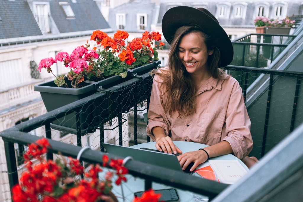 Remote working woman working on balcony with laptop computer